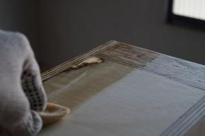 Pessoa aplicando óleo de linhaça em uma peça de madeira